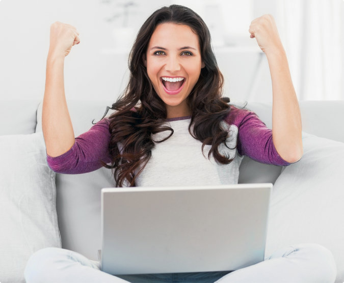 Young independent woman raises both fists in victory while seated on couch with laptop