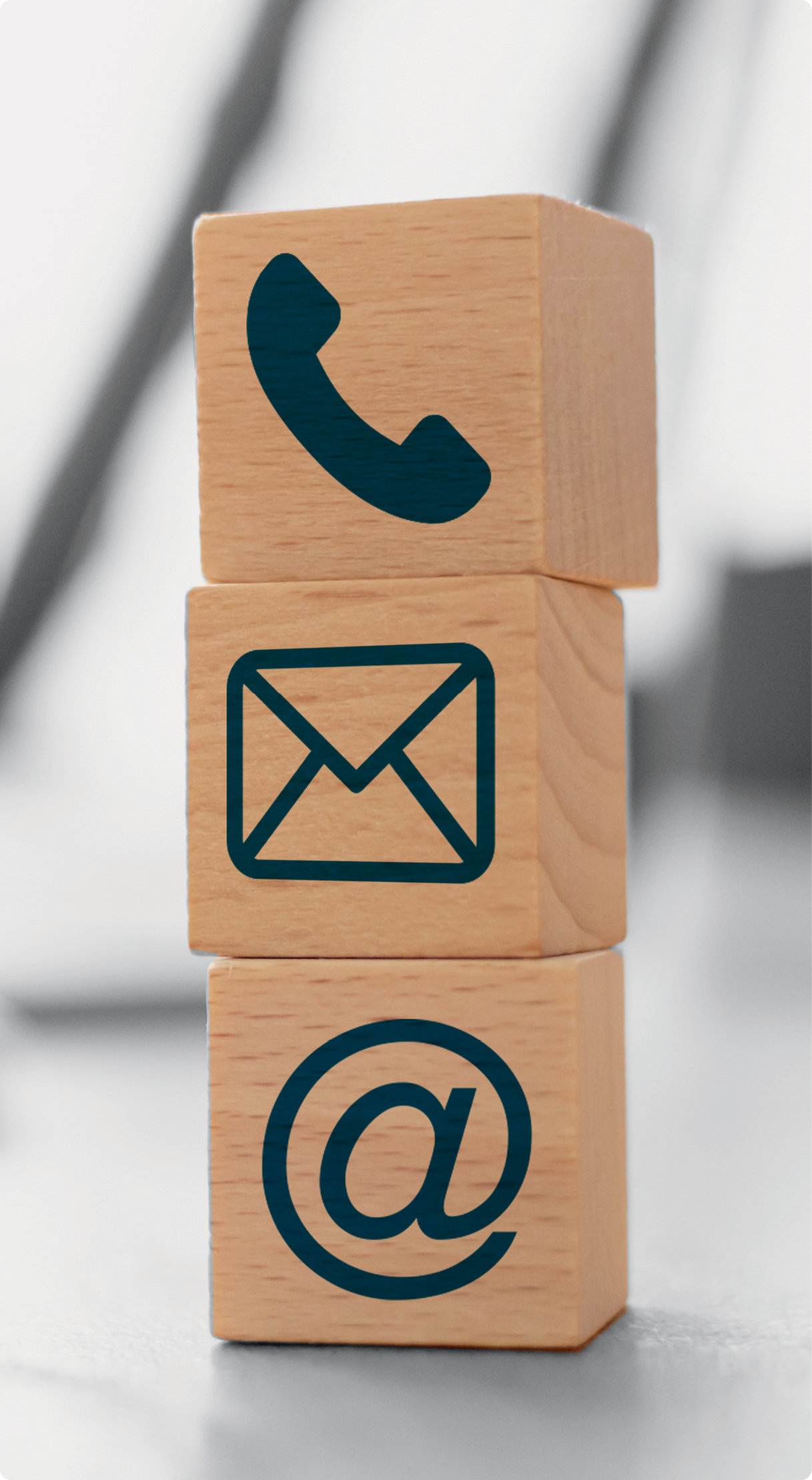 Three stacked wooden blocks with telephone, mail, and email icons inscribed on each