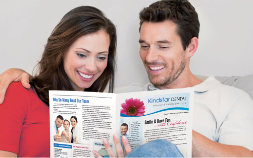 Charismatic middle-aged couple snuggles and reads dental patient newsletter