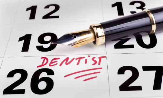 Closeup of calendar with dental appointment noted and fountain pen beside it