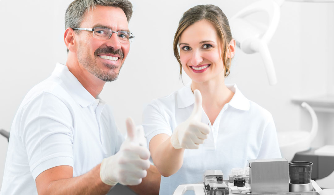 Dentist and team member give thumbs-up sign